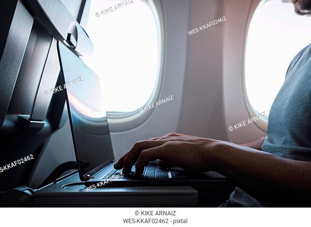 Man using laptop in airplane