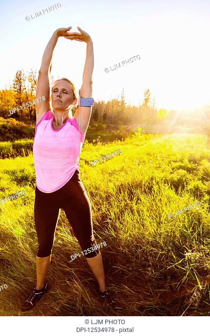 An attractive middle-aged woman wearing active wear and listening to music while pausing to do some stretch exercises during a run in a city park at sunset on a...