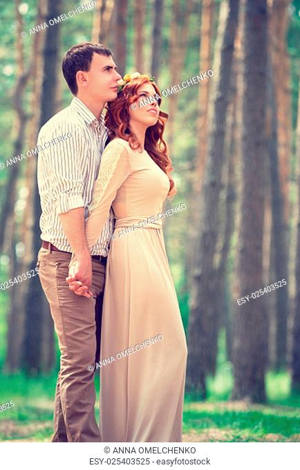 Dreamy couple in the park, stylish bride with groom dreamy looking up in the sky, posing for wedding photoshoot, love and fashion concept