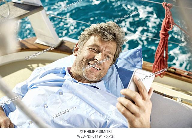 Portrait of smiling mature man lying on deck of his sailing boat looking at cell phone