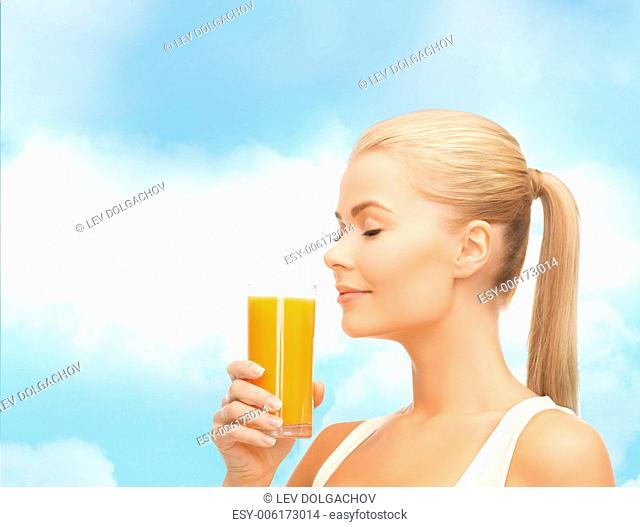 food, healthcare and diet concept - young woman drinking orange juice