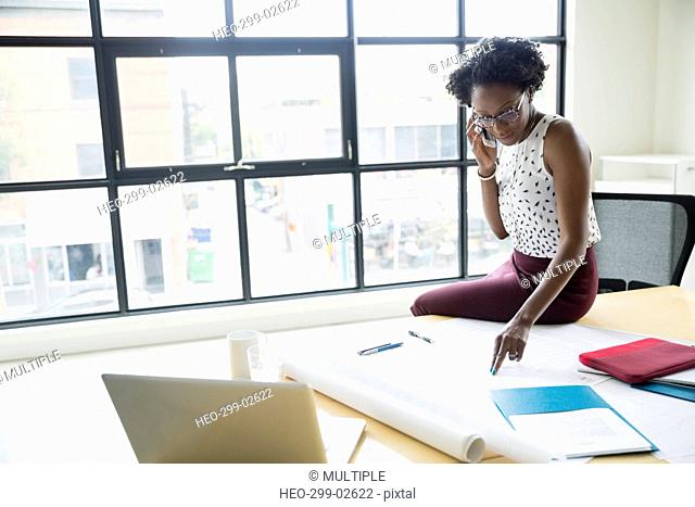 Female architect reviewing blueprints talking on cell phone in conference room