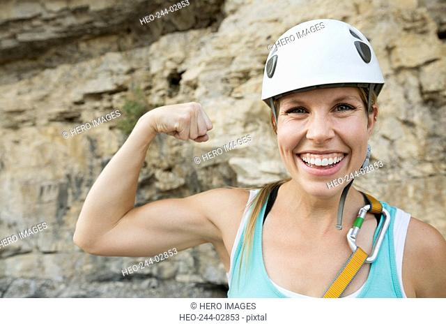 Portrait confident female rock climber flexing biceps