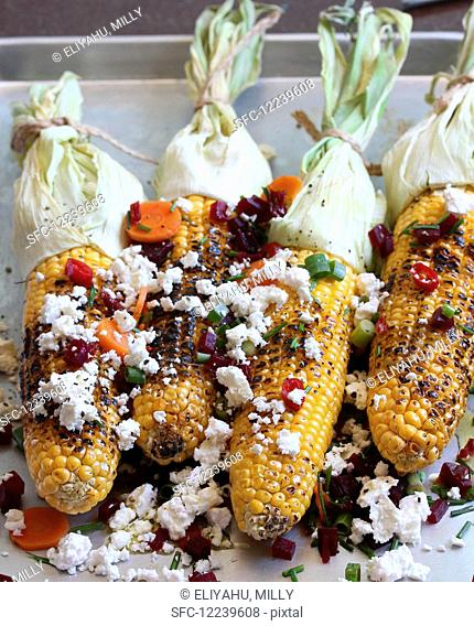 Grilled corn on the cob with vegetables and feta
