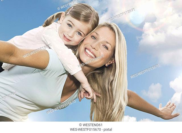 Germany, Cologne, Mother carrying her daughter 2-3 Years on back, smiling, portrait