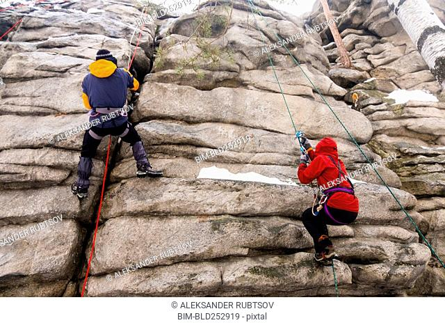 Caucasian man and woman rock climbing