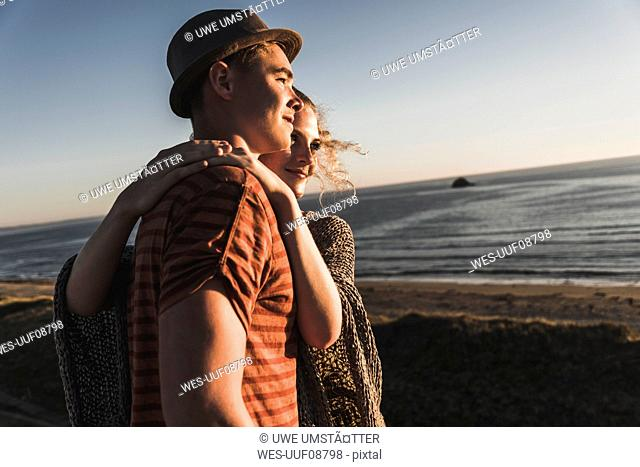 Young couple in love watching sunset on the beach