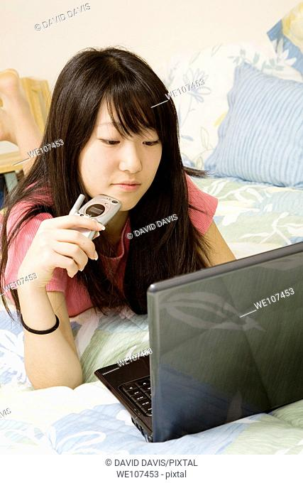 Asian American teen working on laptop computer and talking on cell phone