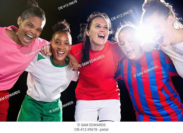 Portrait enthusiastic, confident young female soccer team bonding and cheering in huddle