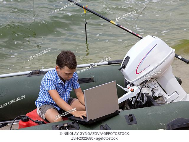 Teenager on a picnic by the river alone with a laptop