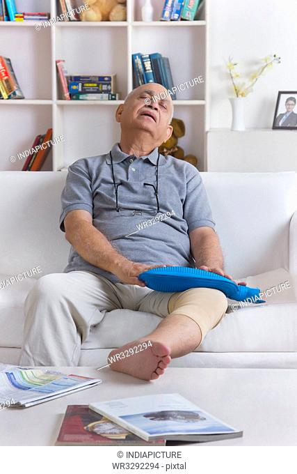 Old man with hot water bag on leg
