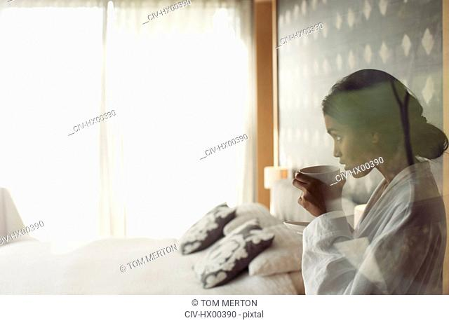 Woman in bathrobe sipping coffee in bedroom