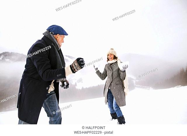 Senior couple having a snowball fight in the snow