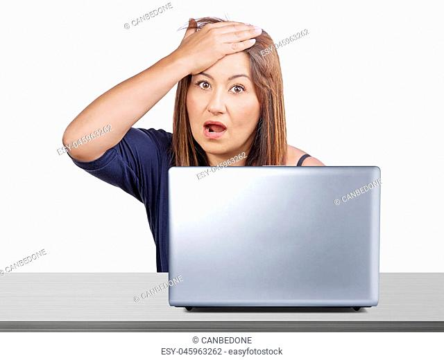 Worried woman working at desk with laptop gesturing forgotten something or regret for mistake isolated