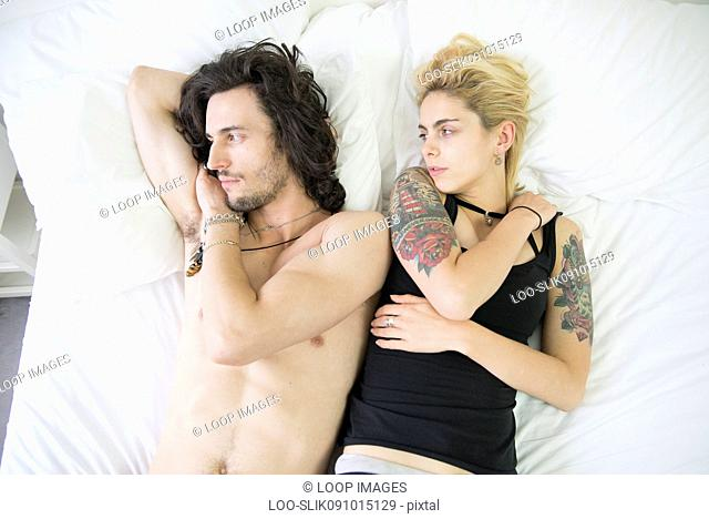 A young tattooed couple lying on a bed after an arguement