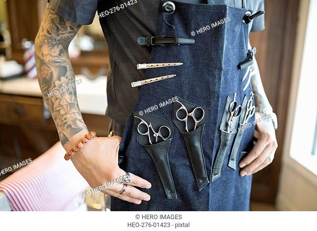 Midsection tattooed barber wearing apron with tools