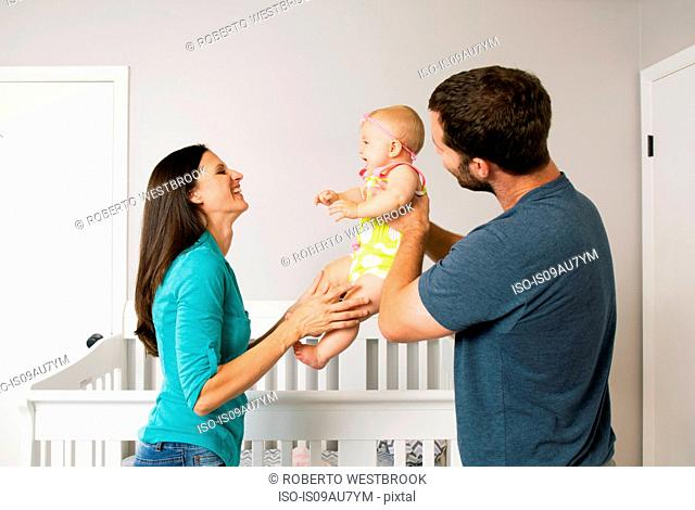 Mid adult couple holding up baby daughter in nursery