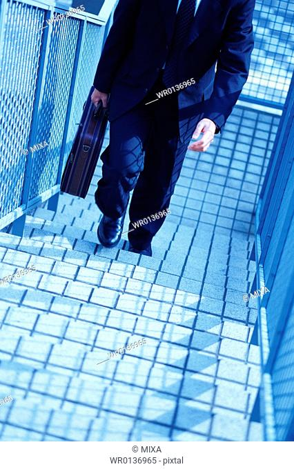 High angle view of a mature man climbing stairs outside