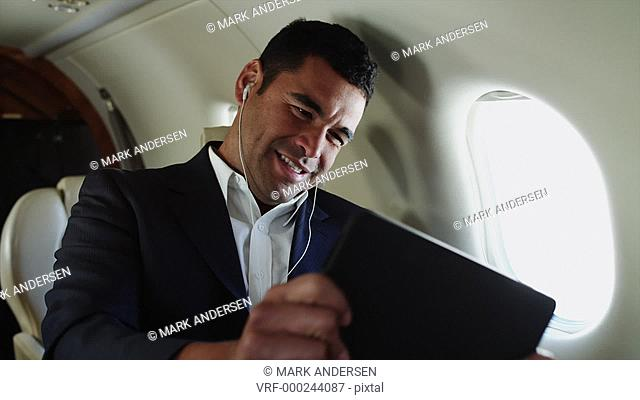 MS Smiling businessman playing with digital tablet in airplane / Spanish Fork, Utah, USA