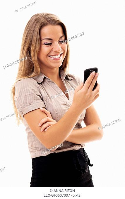 Cheerful businesswoman texting on mobile phone, Debica, Poland