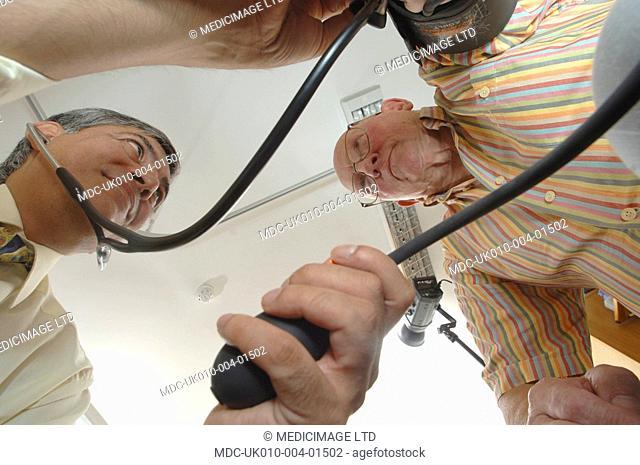 A GP checks an elderly male patient's blood pressure using a sphygmomanometer