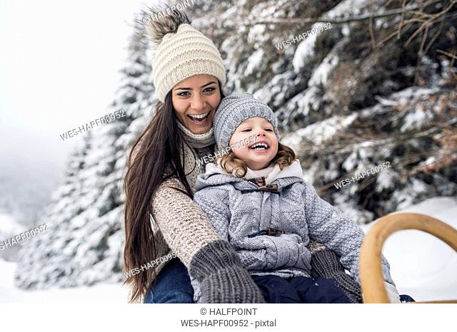 Happy mother with daughter on sledge in winter landscape