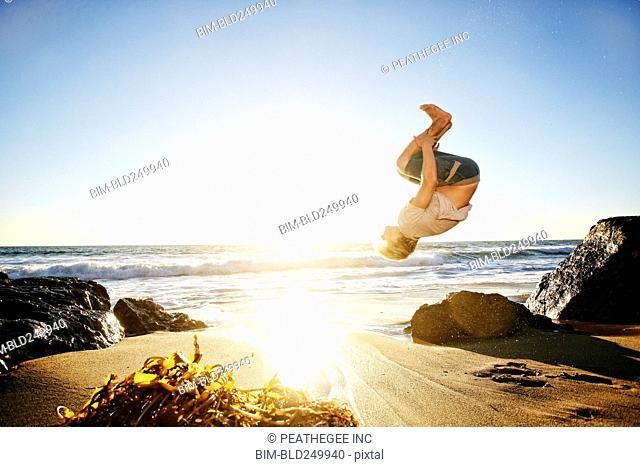 Caucasian man performing backflip on beach