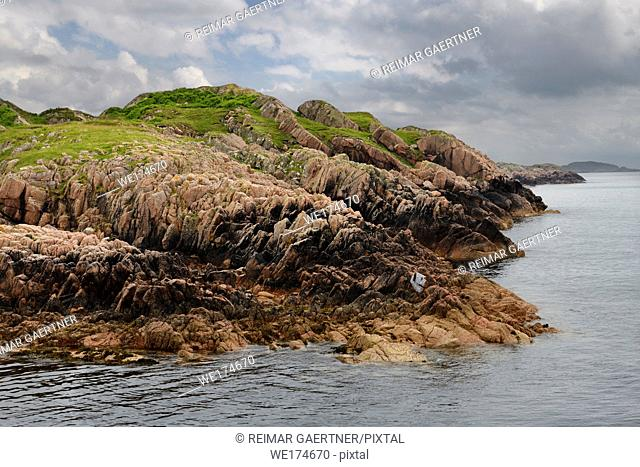 Red Granite outcrop on shore of Sound of Iona at Fionnphort fishing village on Isle of Mull Scotland UK