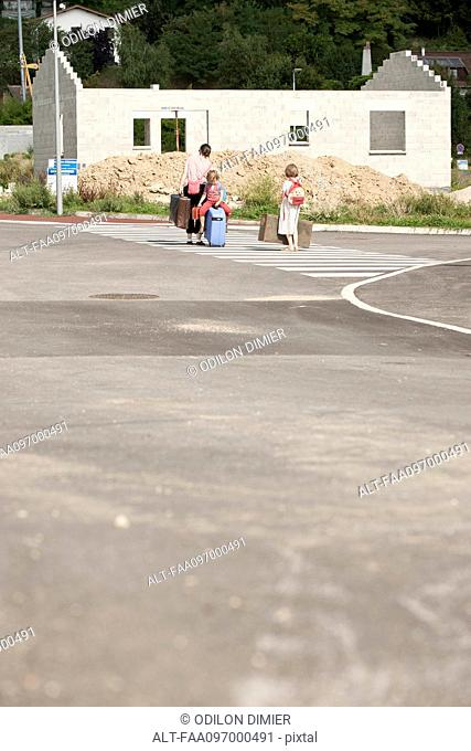 Mother and children walking in street toward unfinished house , dragging suitcases behind them