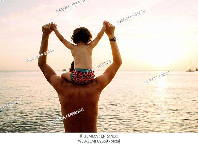 Thailand, Koh Lanta, back view of father with baby girl on his shoulders watching sunset on the beach