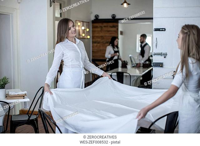 Restaurant staff preparing tables for service