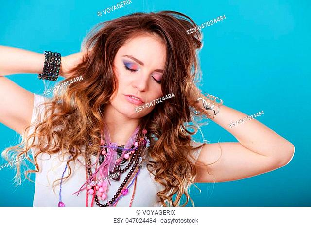 Pretty young woman wearing many plenty of jewelry necklaces beads, rings and bracelets. Portrait of gorgeous fashion girl in studio on blue