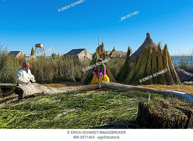 Uros working on the floating islands of the Uros on Lake Titicaca, Puno Region, Peru