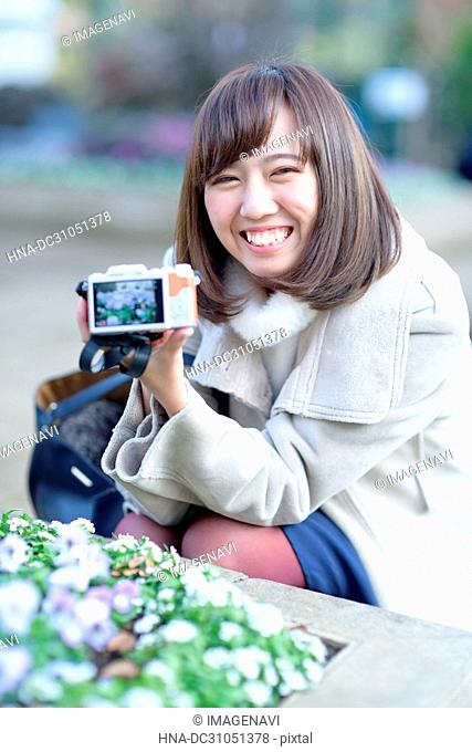 A smiling woman showing her photo taking by digital camera