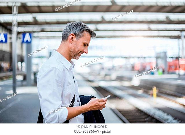 Mature man standing on station platform, looking at smartphone