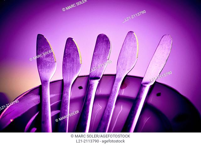 Knives on a stack of dishes