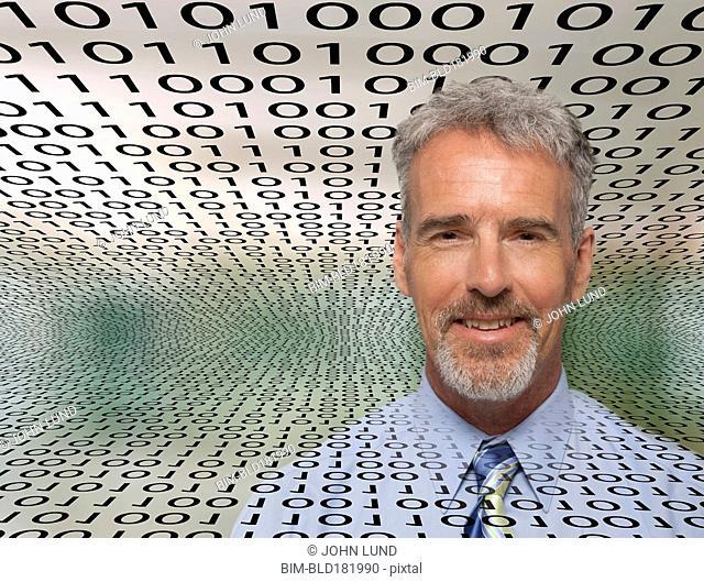 Caucasian businessman in streams of binary code
