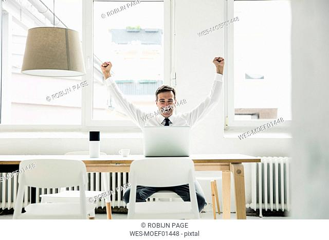 Laughing businessman with laptop on table cheering in office