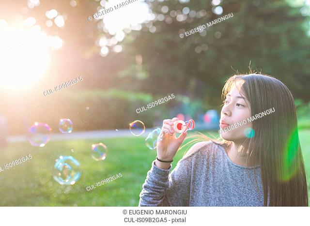 Young woman in sunlit park blowing bubbles