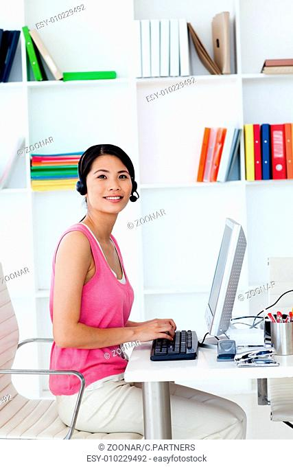 Smiling businesswoman with headset on in the office