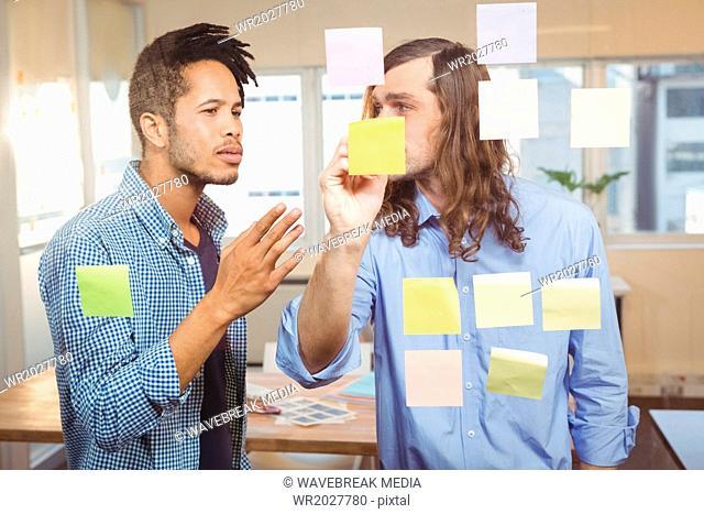 Businessman explaining colleague over sticky notes