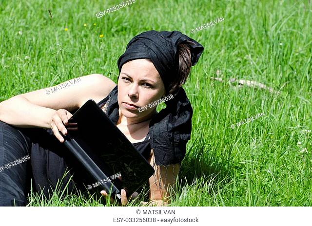 Woman lying down on the green grass with her computer
