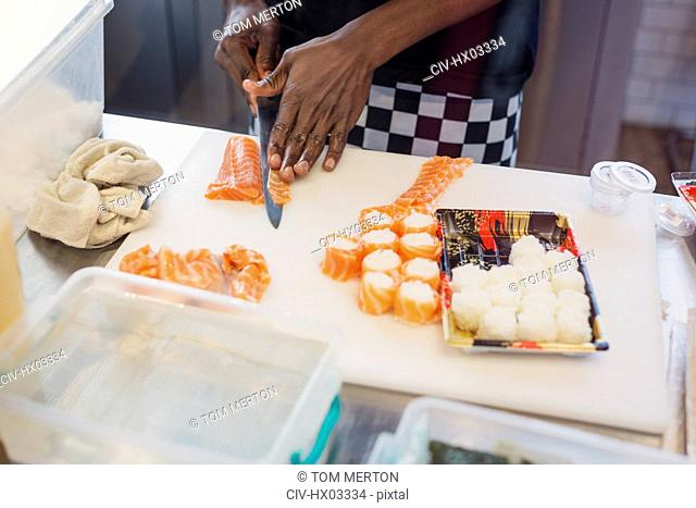 Young female chef slicing salmon, making sushi in restaurant