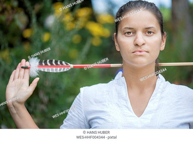 Austria, Salzburg Country, Young woman with arrow, portrait, close up