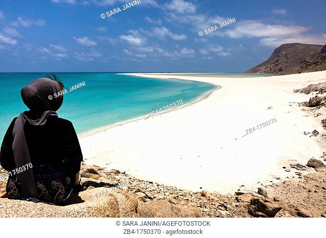 A tourist sitting on a top rock viewing the sand bar on the seaward edge of Ditwah lagoon near Qalansiyah, Socotra island, listed as World Heritage by UNESCO