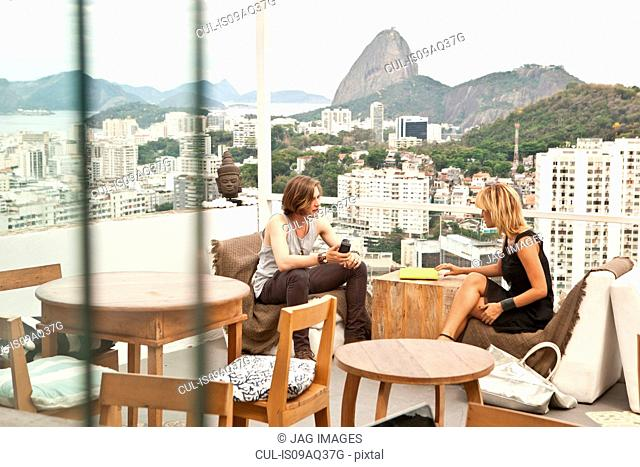 Young couple chatting on rooftop terrace, Rio De Janeiro, Brazil