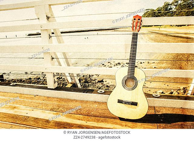Classic music concept on a ocean dock guitar an a old harbour background. Old songs at Shorncliffe Pier, Queensland, Australia