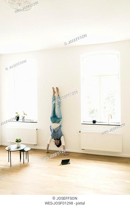 Woman at home doing a handstand at the wall
