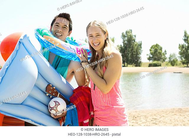 Portrait of cheerful couple with inflatable equipments at lakeshore