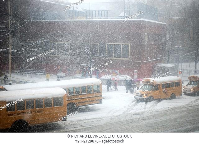 Students pass snow covered school buses as they enter Public School 33 in the Chelsea neighborhood of New York. The NYC Dept